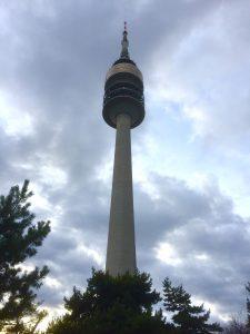 Der Olympiaturm in München umflogen von Wolken.