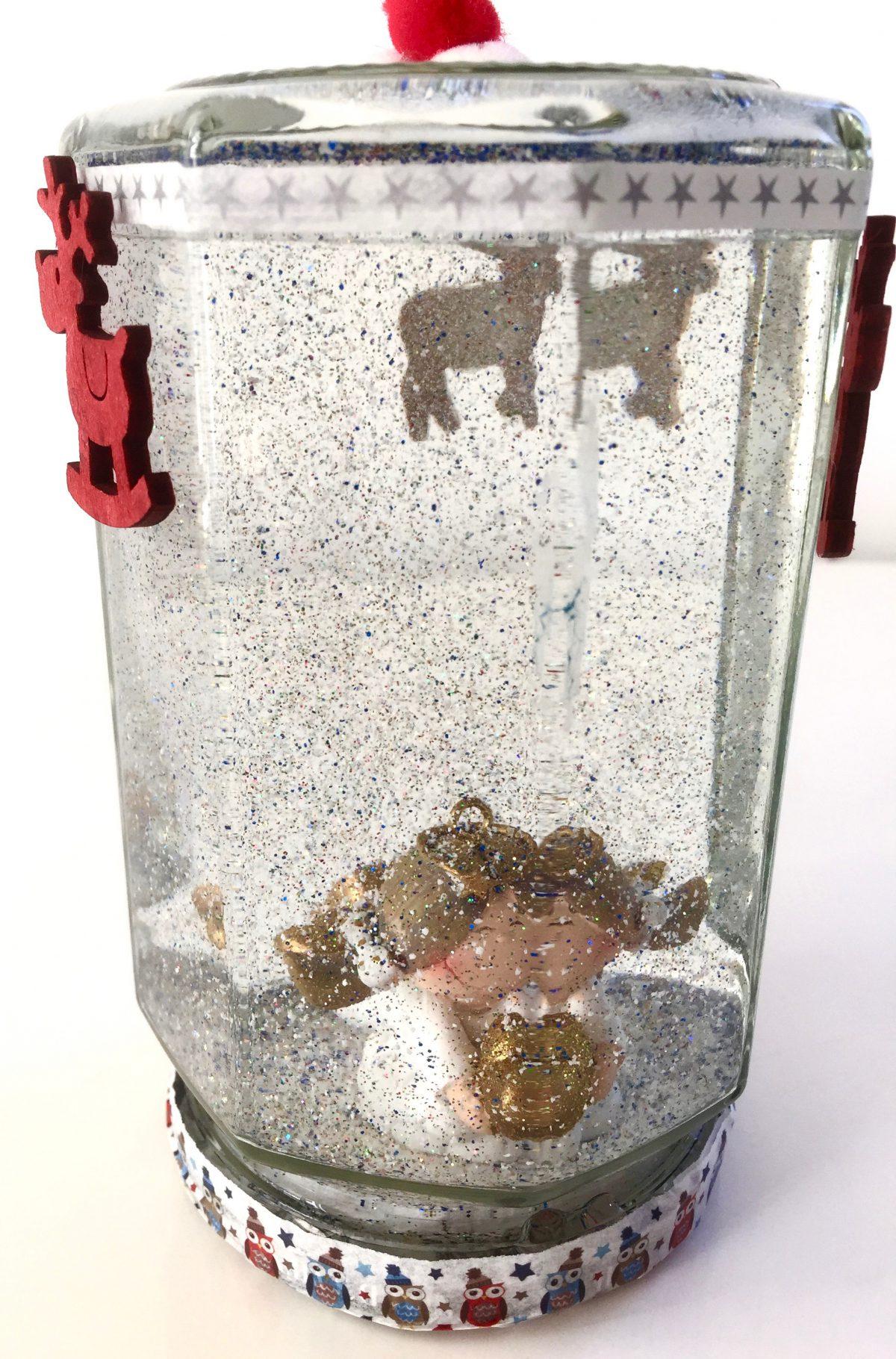 Selbstgemachte Schneekugel mit Engel. Das Glas ist von außen mit roten Rentieren & weihnachtlichem Klebeband.