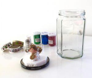 Material für die Schneekugel wird gezeit: Glas mit Deckel, in dem Styropor & ein Engel geklebt sind; Schneekugelschnee, Glitzer, Klebebänder zum Verzieren.