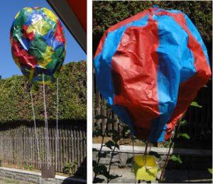 In diesem Bild sind zwei gebastelte Heißluftballons gezeigt. Links ist einer aus Transparentpapier gebastelt. ER ist sehr bunt und hängt in der Luft. Daneben ist ein rot-blauer Ballon aus Seidenpapier. Beiden haben einen Korb am Ende einer Schnur hängen.
