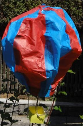 Selbstgebauter Heißluftballon in blau-rot. Er hängt in der Luft mit einem gelben Korb.