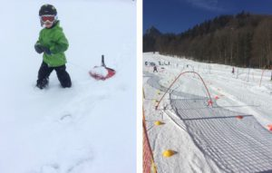 Winterliche Aktivitäten. Zu sehen ist ein Kind, das den Schlitten hinter sich über den Schnee zieht und eine abgesteckte Skipiste, die für ein Kinderskirennen vorbereitet wurde.