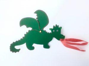 Ein kleiner grüner Feuerdrache mit zwei Flügeln ist zu sehen. Die Flügel sind mit einer Briefklammer befestigt. Aus dem Maul ragen drei rote Feuerstrahlen.