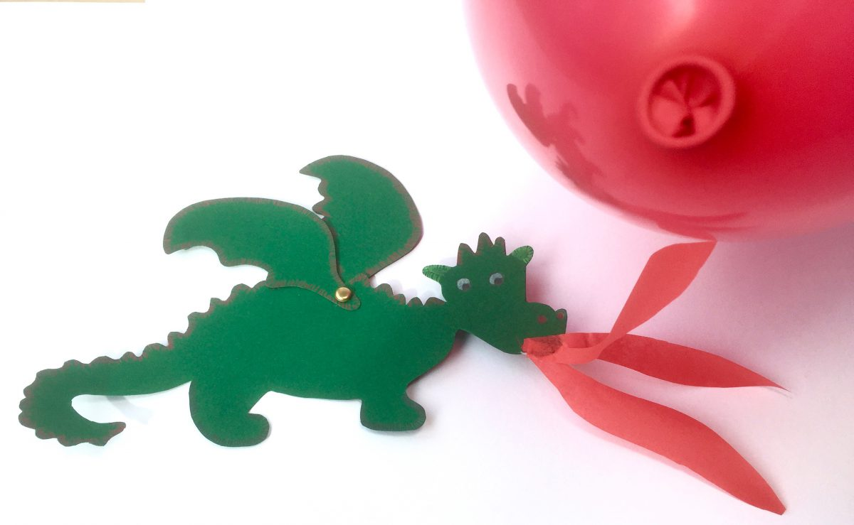 Feuerspeiender Drache in grün aus Pappe gebastelt hat rotes Feuer aus dem Mund heraus, das in die Luft fliegt und sich zum Luftballon hochneigt