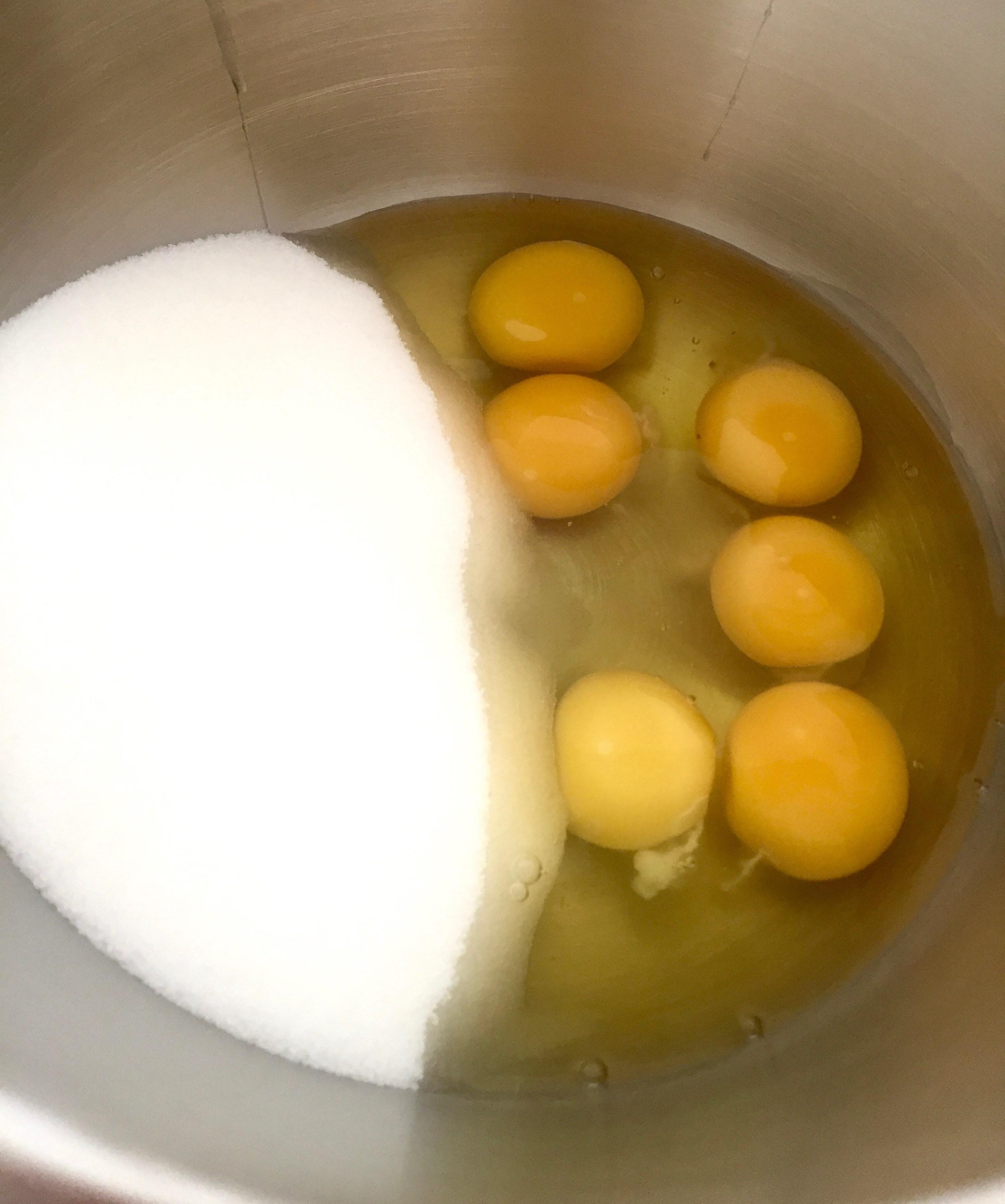 6 Eier und Zucker liegen in einer Rührschüssel vorbereitet.