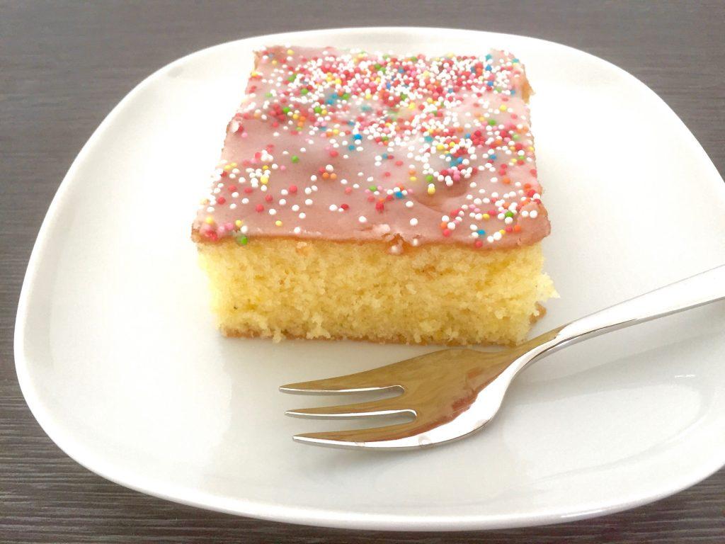 Ein Stück Zitronenkuchen mit Zuckerglasur und bunten Zuckerperlen liegt auf einem weißen Teller samt Kuchengabe.