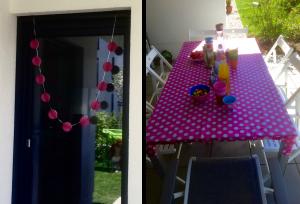 Die Partydeko ist pink. Als Girlande an einer Glastüre, eine pinke Tischdecke mit weißen Punkten. Auf dem Tisch stehen Getränke & Gefäße mit Süßigkeiten und Obst bereit.