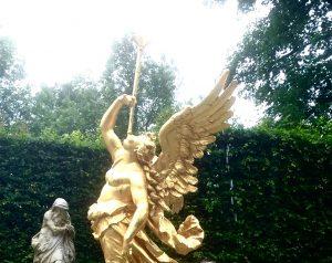 Eine goldene Engelsfigur mit Flügeln hält einen Amorpfeil im Mund, aus dem Wasser sprudelt.