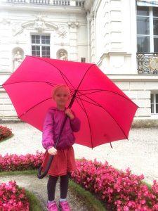 Vor dem Schlossgebäude steht ein Mädchen in pink-farbenen Anziehsachen und mit pink-farbenm Regenschirm. Um das Kind herum sind pinke Blumenbeete angelegt.