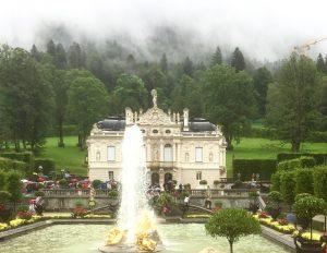 Schloss Linderhof im Überblick mit Fontäne im Vordergrund. Bunte Blumen säumen das weitläufige Wasserbecken.