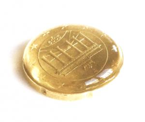 Eine 50 Cent Münze ist mit Wasser befüllt. Das Wasser formt einen kleinen Wasserberg.
