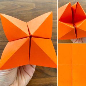 Himmel und Hölle Faltspiel. Beispiel aus orange farbenem Papier ist gezeigt.