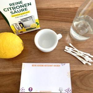 Forschen für Kinder zeigt das Material, das für eine Geheimtinte aus Zitronensaft oder Zitronensäure benötigt wird. Zitrone oder Zitronensäurenpulver, eine Gefäß, eventuell Wasser, Q-Tipps als Pinsel und ein Stück Papier für die geheime Botschaft.