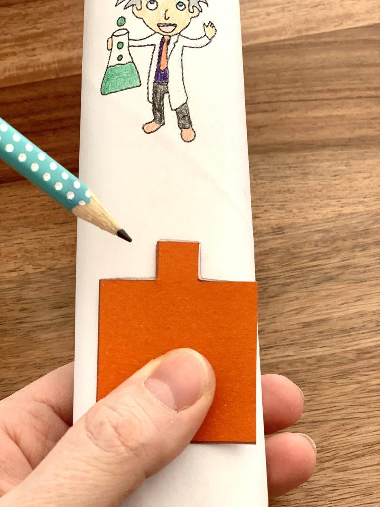 Aufmalen der Markierung entlang des vorbereiteten Pappstücks mit Nase. Die Nase zeigt immer vom Ende der Papprolle weg.