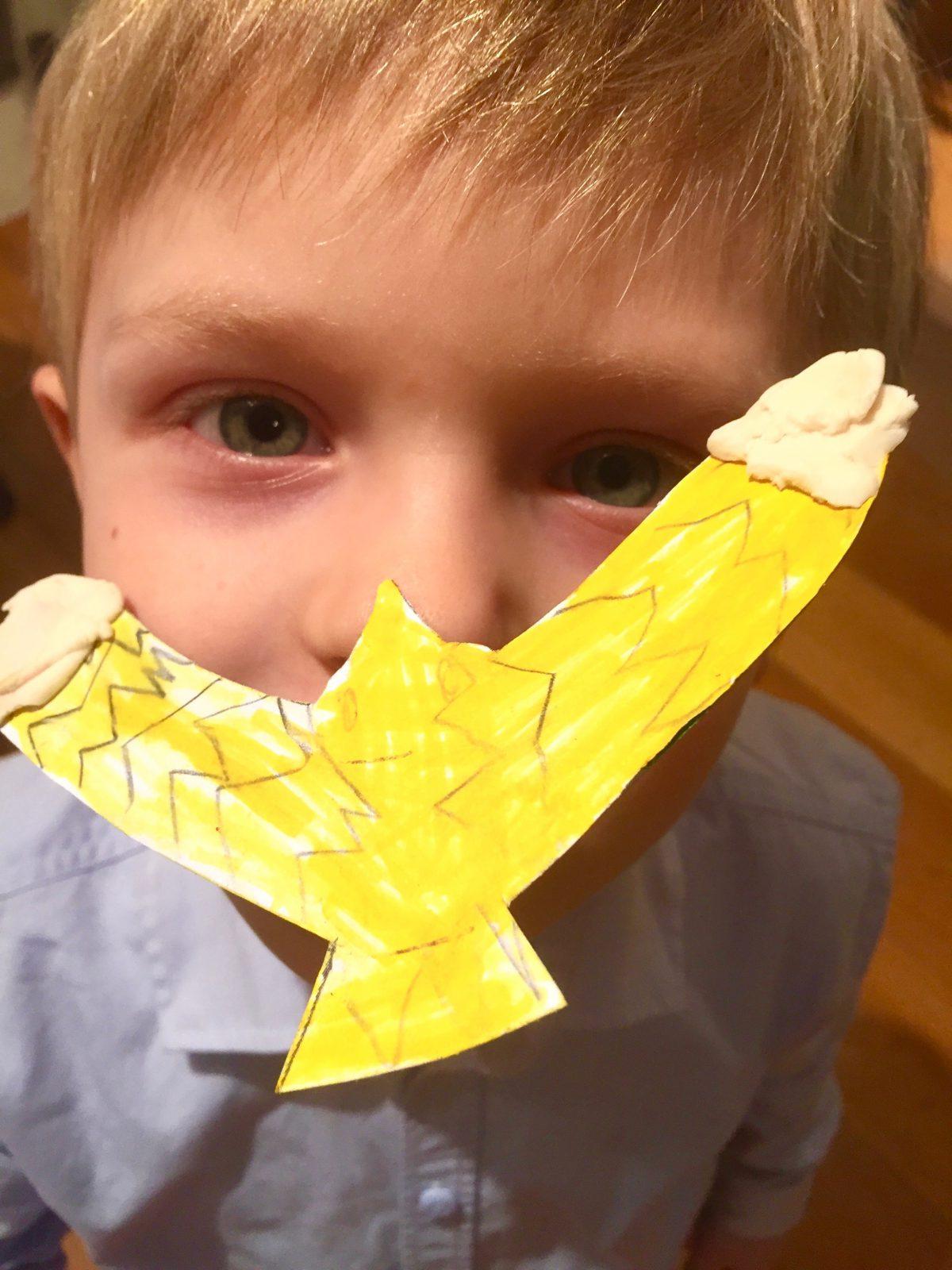 Ein gebastelter Zaubervogel, gelb bemalt, schwebt auf der Nase eines Kindes.