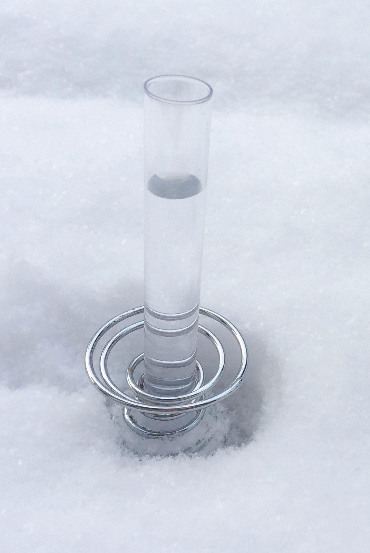 Ein Wasserglas steht im Schnee.