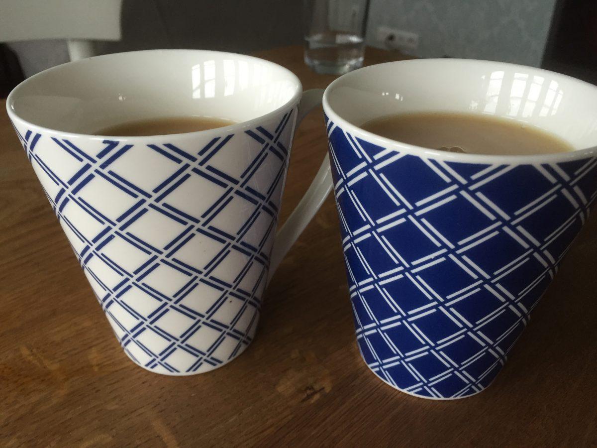 Zu sehen sind zwei Teetassen. Eine weiß mit blauem Karomuster, eine blau mit weißem Karomuster. Beide sind mit Schwarztee gefüllt