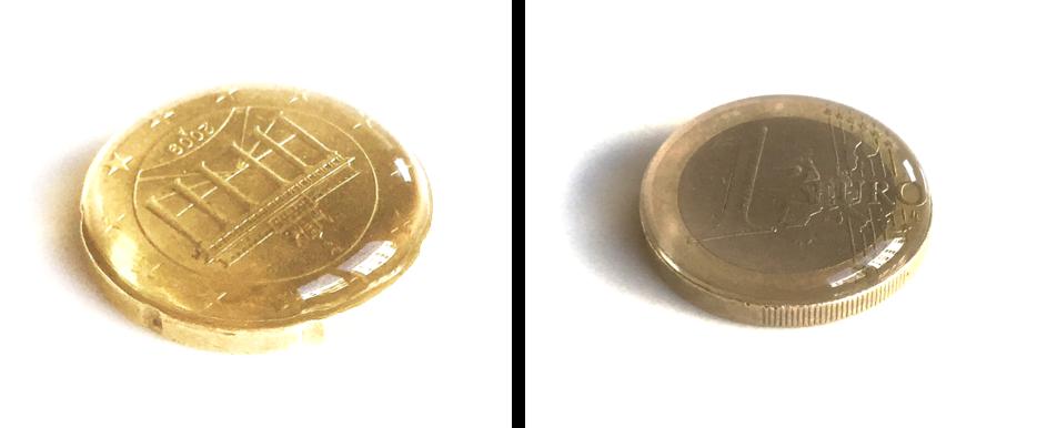 Zu sehen sind zwei Geldmünzen. Links die Rückseite einer 50 Cent-Münze, rechts die Front einer 1 Euro-Münze. Auf beiden ist Wasser gefüllt, das einen kleinen Wasserberg bildet, aber nicht überläuft.