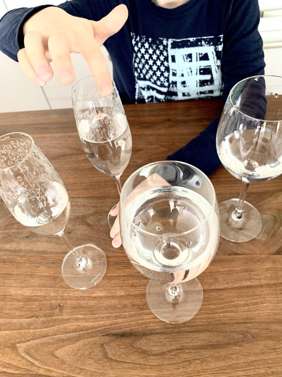 Mit Wasser gefüllte Weingläser und Sektgläser stehen auf einem Holztisch. Eines wird mit dem Finger am Glasrand umkreist, um einen Ton zu erzeugen.