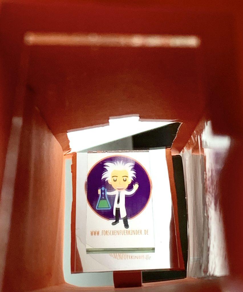 Ein Blick durch das Periskop zeigt klar und deutlich das Bild, das von einer Öffnung über die beiden Spiegel ins Auge des Betrachters gelenkt wird. Zu sehen ist das Forscherlogo von Forschen für Kinder.