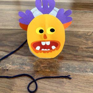Kleines, kreatives Monstergesicht auf einem Plastikbecher zum Erforschen von Geräuschen