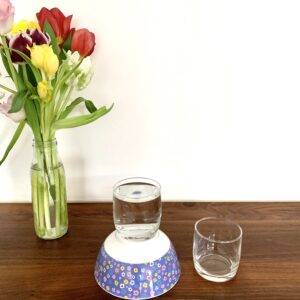 Wasserexperiment: Wasserglas steht erhöht und ein zweites. leeres Wasserglas steht etwas tiefer daneben. Wie kommt das Wasser nun den Berg hinab?