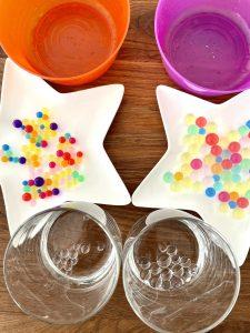 Im Bild sind Wasserperlen auf weißen Sternentellern zu sehen. Links (orangene Seite) sind die Perlen kleiner als rechts (lilafarbenen Seite). Transparente Perlen wurden in ein leeres Glas überführt, das davor steht.