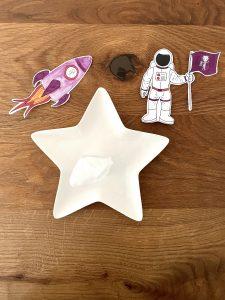 Ein Sternenteller mit aufrecht stehendem Teebeutel und einem Bild eines Astronauten sowie einer Rakete sind zu sehen.